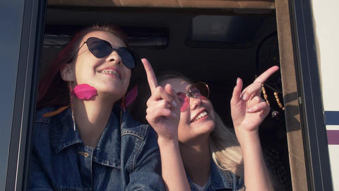 a pair of young women in sunglasses are smiling in the window of a trailer at Footage