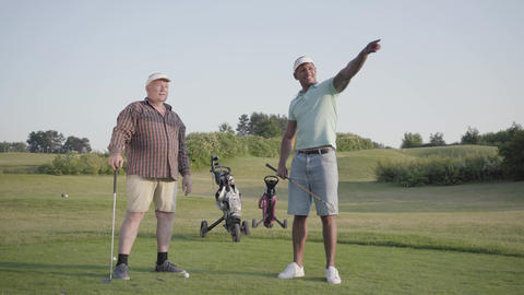 Mature Caucasian man and young middle eastern man playing golf on the golf Footage
