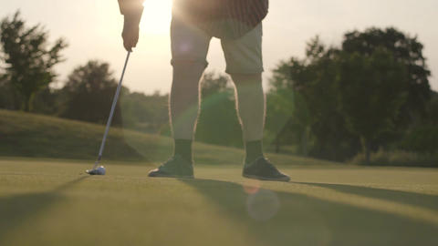 Golf ball lying on the grass in the sun rays. Unrecognized mature man moving the Footage