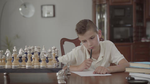 Portrait of adorable thoughtful guy sitting at the table at home. Boy dawned on Footage