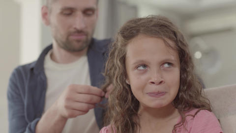 Dad braids curly hair cute little daughter. Family relationships Footage