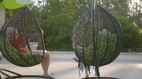 Grandmother and grandfather resting on hanging chairs in the sun. Happy friendly Live Action