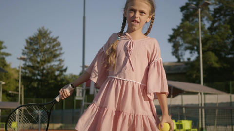 Adorable funny girl with two pigtails playing tennis outdoors. Concentrated Footage