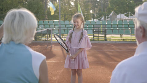 Cute funny girl with two pigtails playing tennis outdoors while her grandparents Footage