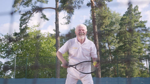 Positive smiling mature man playing tennis on the tennis court. The old man Footage