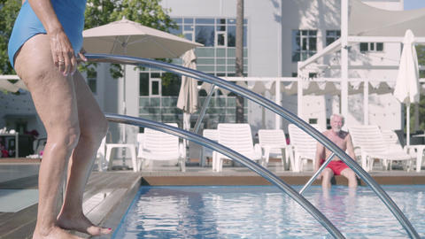 Attractive senior woman walking into the pool while her husband sitting in the Footage