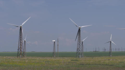 work of wind turbines placed in the fields against a blue sky Footage
