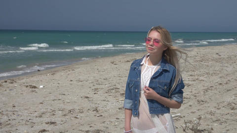 young blond woman in pink sunglasses against the sea and blue sky Slow motion Footage