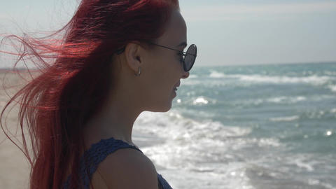 profile portrait of a young woman with red hair flying in the wind in sunglasses Live Action