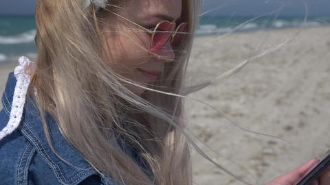 young blonde woman in denim jacket on the background of the sea and the beach Footage
