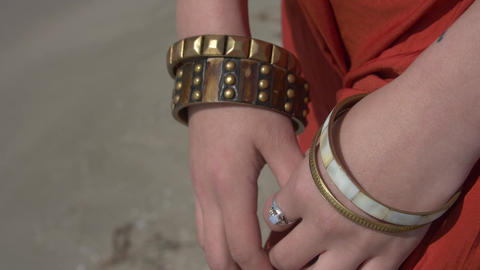female hands with a ring on a finger and in bracelets of bronze color Footage