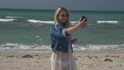 young blonde woman in a translucent white dress and denim jacket makes a photo Footage
