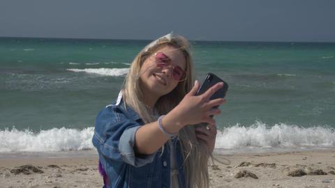 young blond woman in a denim jacket on the background of the sea speaks by video Footage