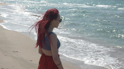 slow motion redheaded young woman in a red skirt is standing on the beach and Footage