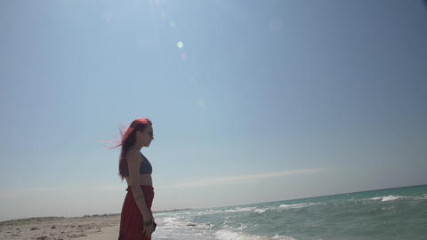 red-haired young woman in sunglasses stands in a strip of sea surf Footage