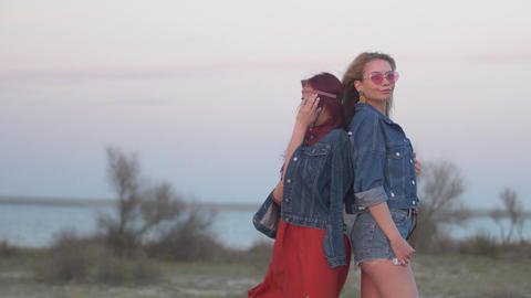 slow motion two young women dressed in denim jackets stand back to back with Footage