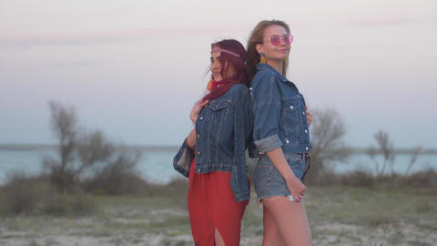 two young women dressed in denim jackets stand back to back in the gentle rays Live Action