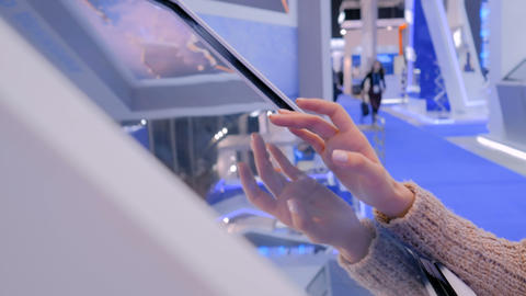 Woman using interactive touchscreen display at technology exhibition Live Action