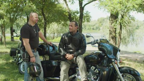 Positive male bikers chatting near motorbike Footage
