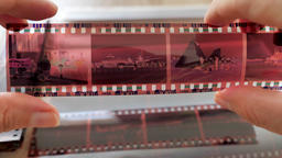 Man is watching vintage photographic film strip Footage