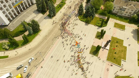 Aerial view of the solemn parade of dance groups marching along main streets of Footage