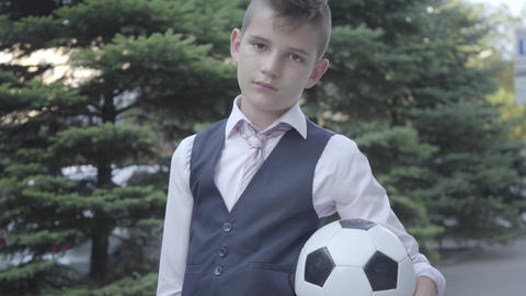 Portrait cute well-dressed boy standing on the street holding the soccer ball Footage