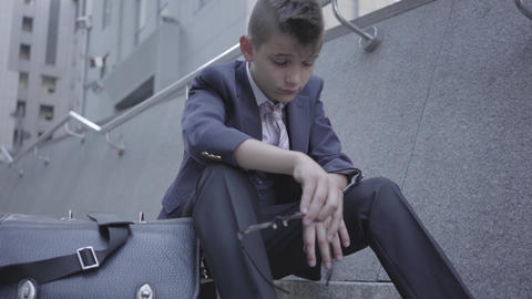 Sad well-dressed boy sitting on the stairs on the street, old purse near him Footage