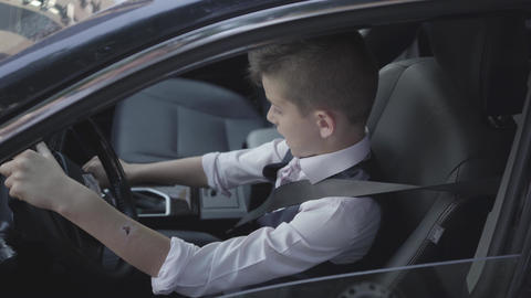 The young well-dressed boy learning to drive the car sitting at the drivers seat Footage