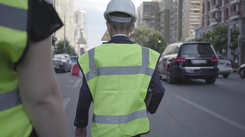 Little road worker or inspector wearing safety equipment and constructor helmet Footage