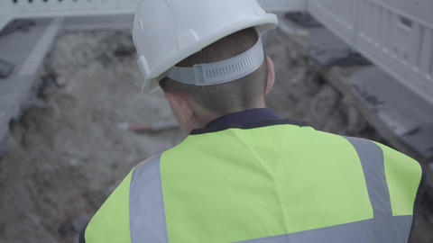 Little successful boy wearing safety equipment and constructor helmet standing Footage