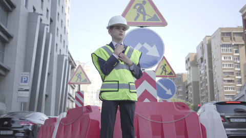 Portrait cute little boy wearing business suit and safety equipment and Footage