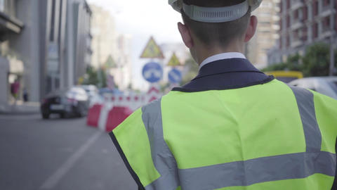 Little boy wearing safety equipment and constructor helmet walking on a busy Footage