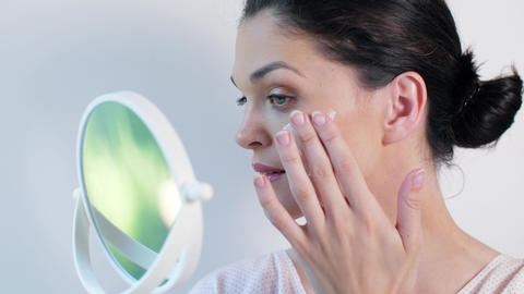 Woman applying cosmetic cream treatment on her face Footage