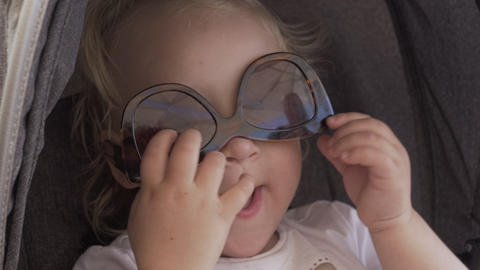 A closeup of a baby girls face who is wearing female sunglasses upside down Live Action