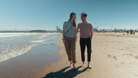 A happy couple walking down the beach barefoot holding hands Live Action