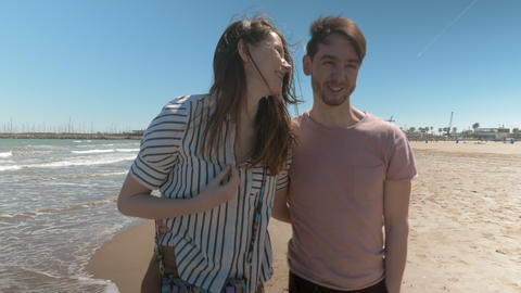 A smiling couple walking along the beach on a sunny day Footage