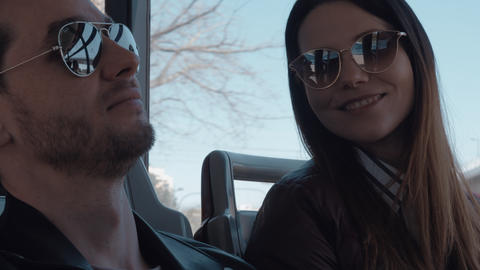 A couple in sunglasses sitting in a moving bus and talking Live Action
