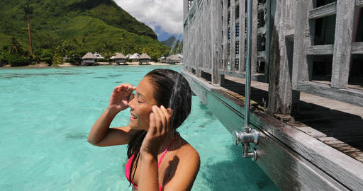 Luxury travel destination bikini woman taking an outdoor shower at resort hotel Footage