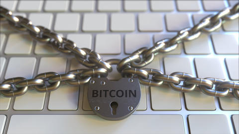 Chains and padlock with BITCOIN text on the computer keyboard. Conceptual 3D Footage