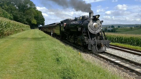 Steam Passenger Train Pulling out of Picnic Area Along Amish Farmlands on a Sunny Summer Day Footage