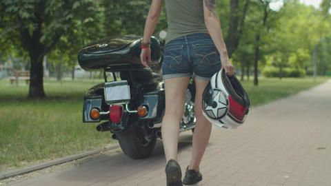 Woman walking to motorcycle with helmet in hand Live Action