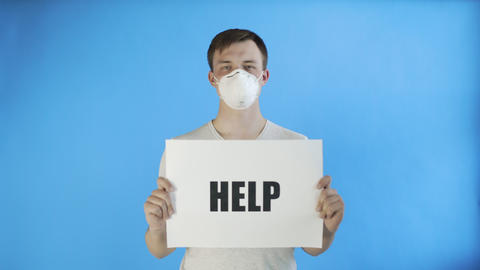 Young Man Activist With mask on face and with HELP Poster on blue background Live Action