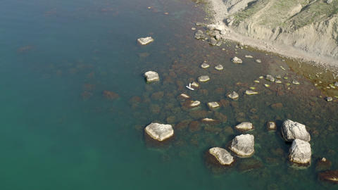 Sup surfer swimming between rocks rising from water. Narrow rocky coastal strip turns into rocky Footage