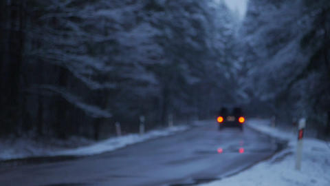 The car rides on a snowy forest road in the evening. Winter time. From the Footage