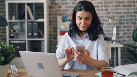 Pretty girl touching smartphone screen and smiling sitting at desk in office Footage
