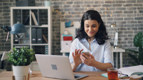 Smiling girl using smartphone watching content on screen in workplace Footage
