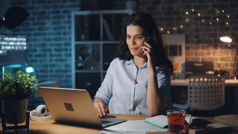 Beautiful office worker chatting on mobile phone in office using laptop at night Live Action
