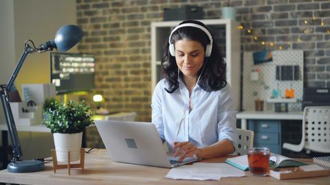 Attractive lady in headphones listening to music at work and working with laptop Footage