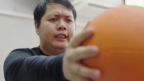 Asian fat man trying to exercise with medicine ball in fitness gym, Healthy lifestyle, weight loss Live Action