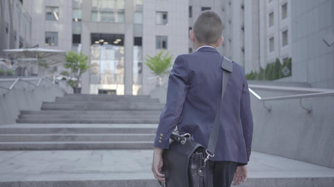 Cute little boy wearing a business suit with case walking in the city. Child as Live Action